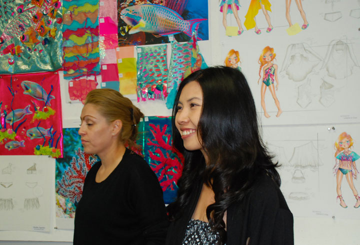 Designer Emily Fong and assistant in front of student sketches