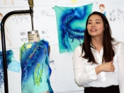 Student in front of her sketches and swimsuit design