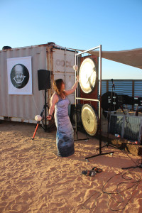 Michelle Chong sounds a gong near a print by Scott Grieger.