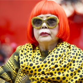 Yayoi Kusama rocks a blazing red bob, oversize sunglasses and polka dots.