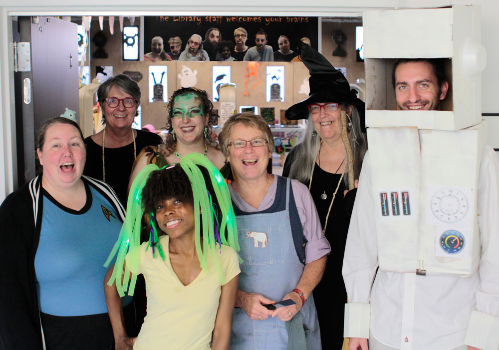 LIbrary-staff-in-costume-under-banner